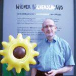 Georg Schober mit Sonnenblume vor dem Bücherschmaus.